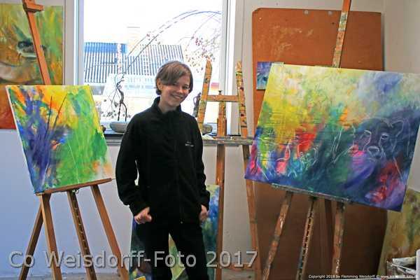 Sara Gepard mellem to ufærdige malerier af geperder, som skal støtte de vilde geparder