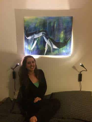 Maleri på bestilling af to pukkelhvaler. kvinden i sofaen under maleriet har fået maleriet som gave.