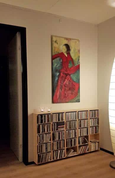 solgt maleri af rød flamencodanser på væggen over bogreol