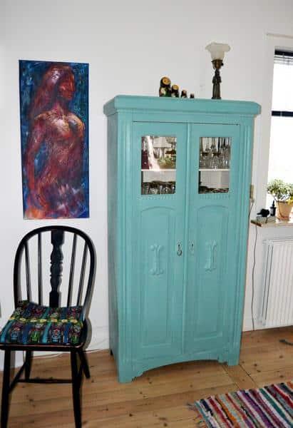 solgt maleri af flamencodanser i blåt og rødt. Hængt på væggen ved siden af skab