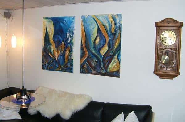 to solgte abstrakte malerier over sofaen. Der er i blå og gule farver