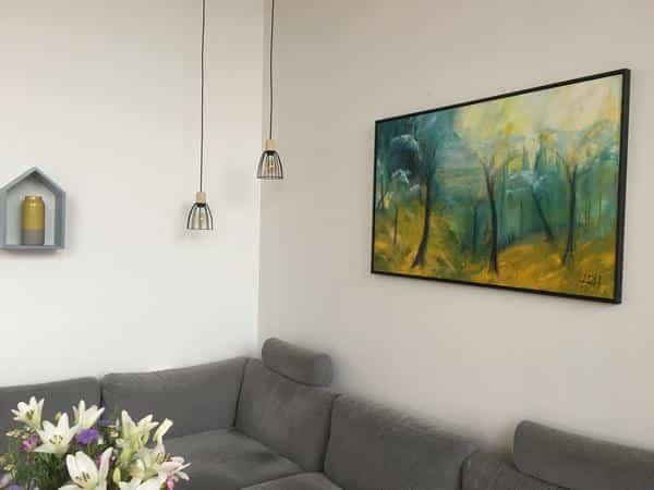 Maleri på bestilling hængt op på kundens væg. Motivet er fra Skuldelev ås udført i farverne blåt, gult og mintgrønt