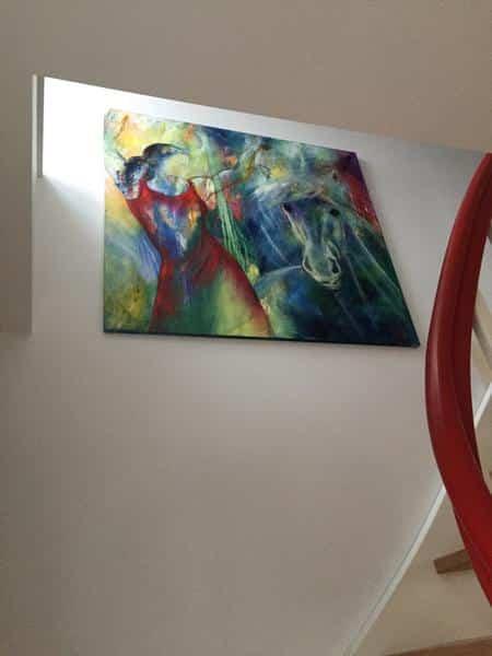 Maleri på væggen på trappen. Farverigt oliemaleri af danser og hest