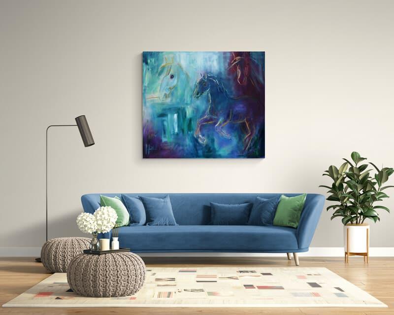 Maleri i blå farver af heste over sofaen